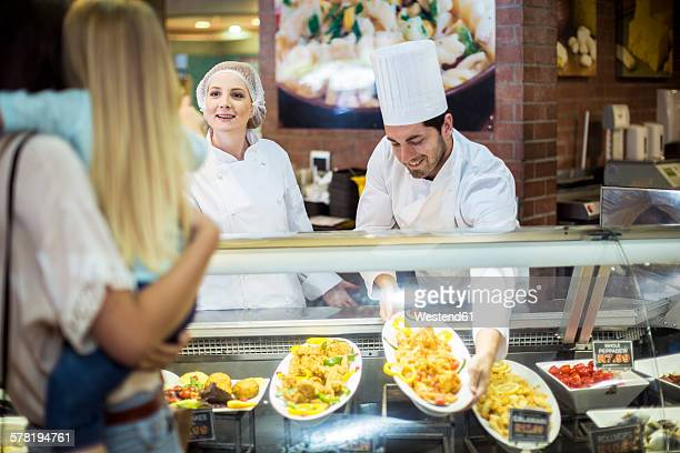 male chef and assistant helping clients at food display - food state stock pictures, royalty-free photos & images