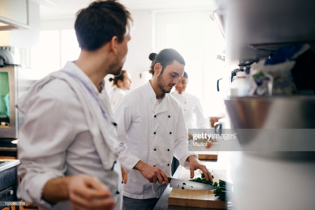 Male chef chopping vegetable in commercial kitchen : Foto de stock