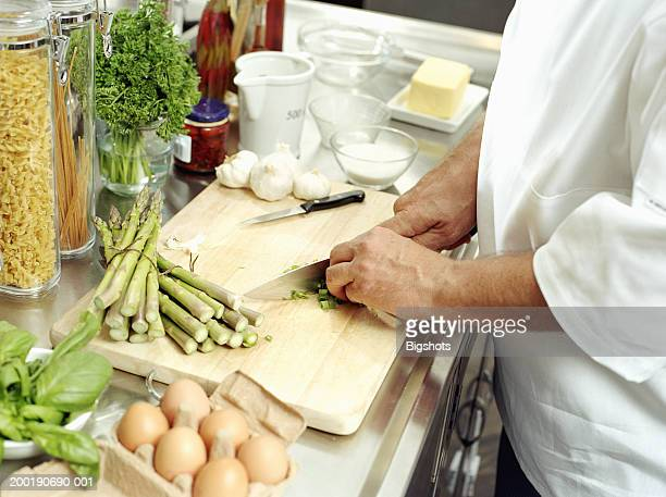 Male chef cutting vegetables on wooden chopping board, mid section