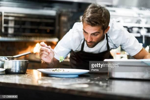male chef garnishing food in kitchen - chef imagens e fotografias de stock