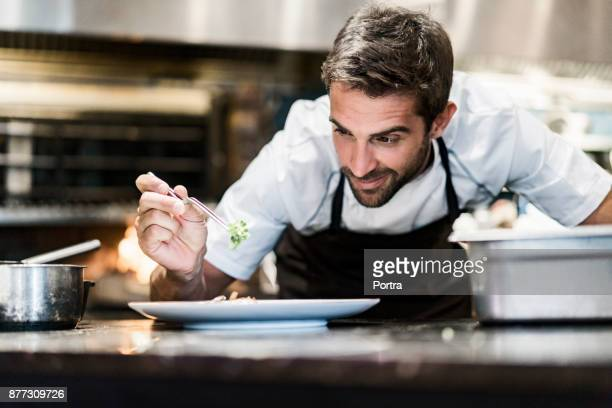 male chef garnishing food in kitchen - food and drink stock pictures, royalty-free photos & images