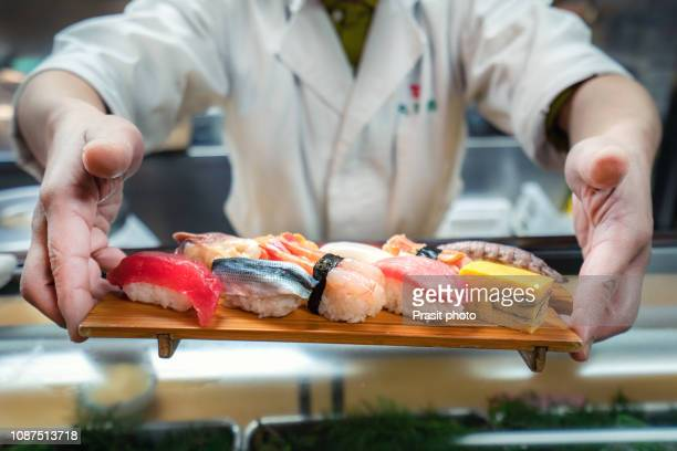 male chef holding a plate full of sushi at the kitchen - sushi stock pictures, royalty-free photos & images