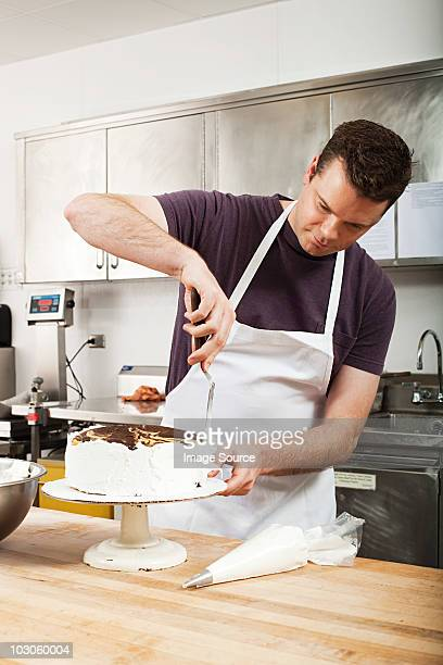 male chef icing a cake in commercial kitchen - decorating a cake stock pictures, royalty-free photos & images