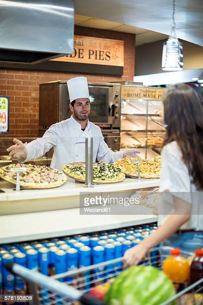 Male chef in bakery serving pizza to female client
