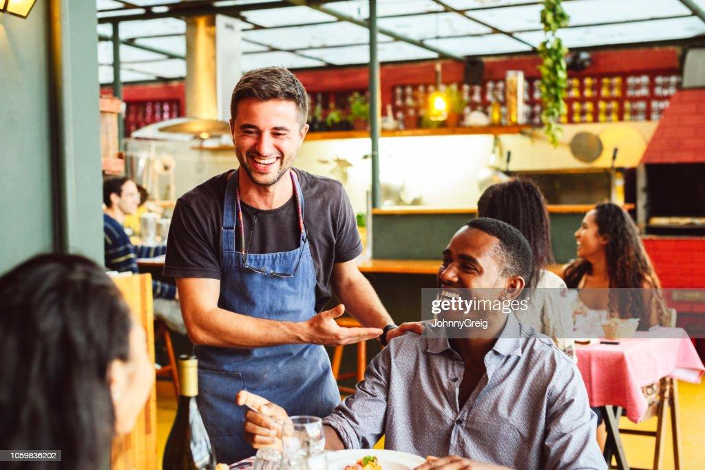 Mannelijke chef-kok lachen en chatten met hand op de schouder van mannelijke klant : Stockfoto
