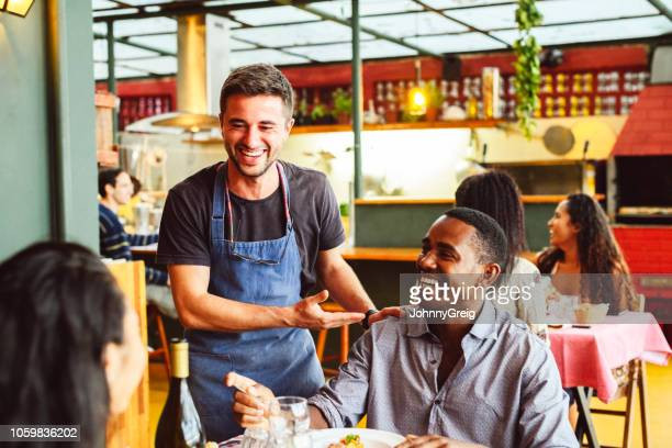 male chef laughing and chatting with hand on shoulder of male customer - food service occupation stock pictures, royalty-free photos & images