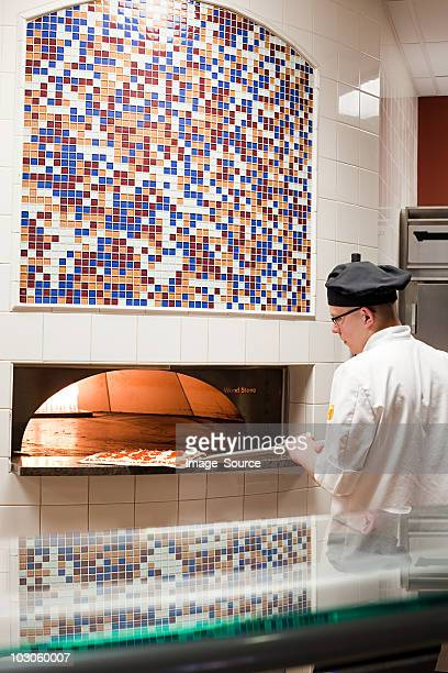 male chef making pizza in commercial kitchen - pizza oven stock photos and pictures