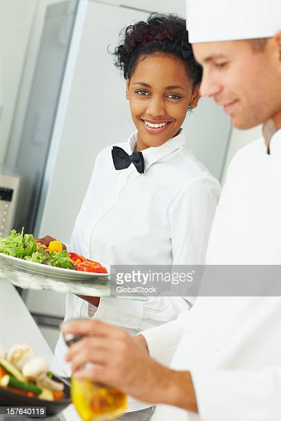 Male chef preparing food while a waitress holding fresh salad