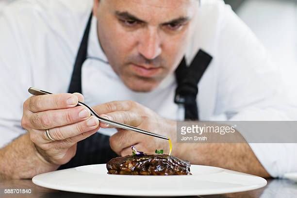 Male chef preparing meal on plate