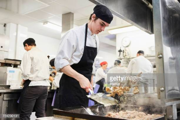 male chef student tossing food with teacher and colleagues in background at cooking school - hot teacher stock pictures, royalty-free photos & images