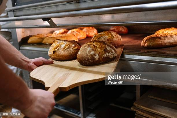 male chef with pizza peel removing baked bread from oven at bakery - bread stock pictures, royalty-free photos & images