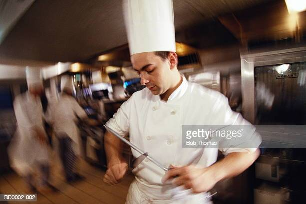 Male chef working in kitchen, sharpening knife (blurred motion)