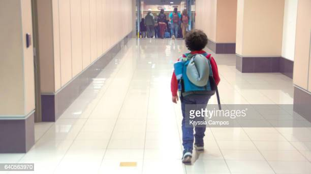 A male child striding out alone on corridor at an airport