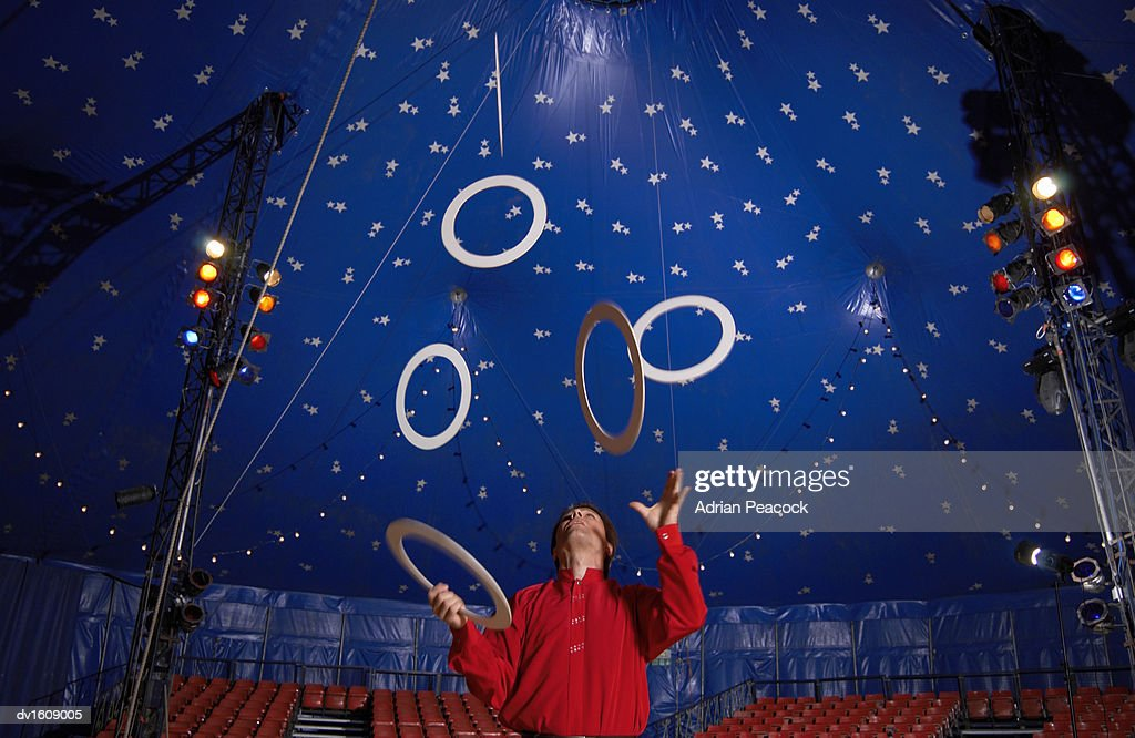 Male Circus Performer Practises Juggling Hoops Inside a Circus Tent : ストックフォト