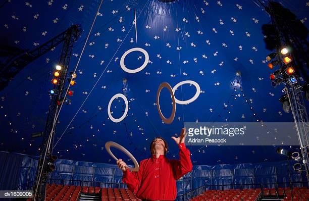 Male Circus Performer Practises Juggling Hoops Inside a Circus Tent