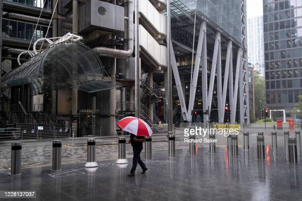 A male City worker carrying a red and white corporate brolly for 'EC3 Brokers' walks through a rain shower outside the lloyds of London building on...