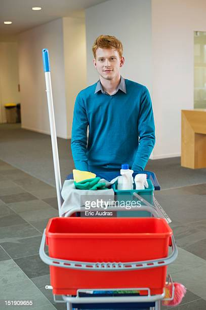 male cleaner pushing trolley with cleaning equipment - janitor stock photos and pictures