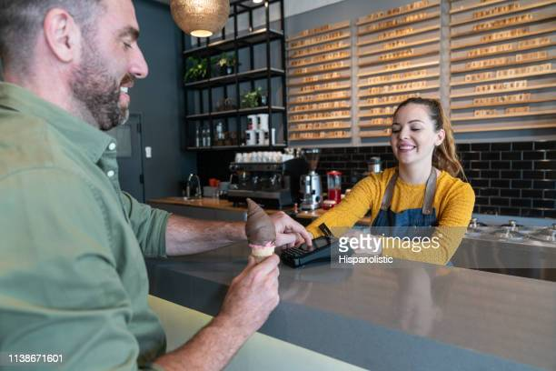 male client at the ice cream parlor paying with credit card while waitress holds credit card reader behind counter - ice cream parlour stock pictures, royalty-free photos & images