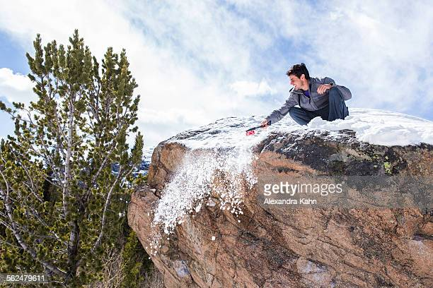 Male Climber cleans snow off the top of a boulder in Rocky Mountain National Park, Colorado