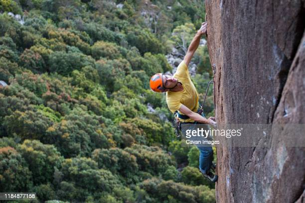 male climber looking up as he ascends a diorite rock wall at the organ pipes, at mt wellington, near hobart, tasmania. - chalk rock stock pictures, royalty-free photos & images