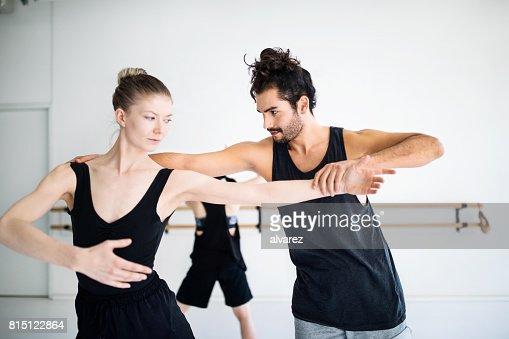 Male coach adjusting posture of female dancer