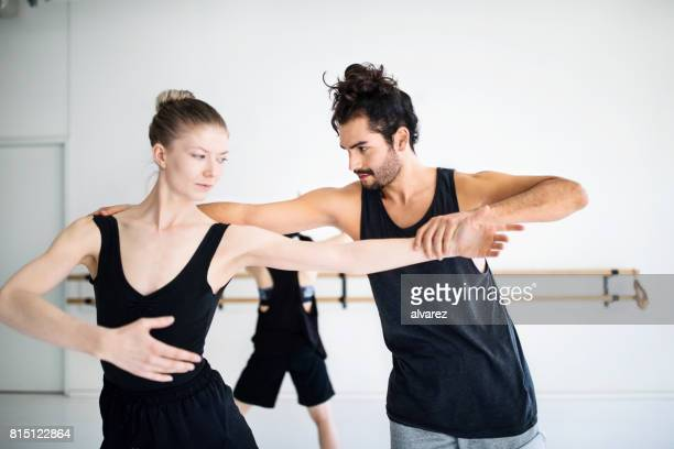 male coach adjusting posture of female dancer - male ballet dancer stock photos and pictures