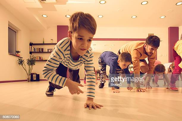 Male coach and kids walking on all fours during training.