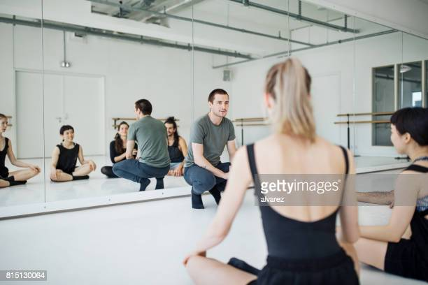 Male coach crouching in front of ballet dancers