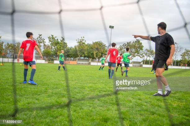 männlicher coach leitet junge fußballer während des trainings - jugendmannschaft stock-fotos und bilder