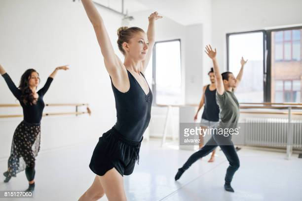 Male coach standing by young dancers at studio