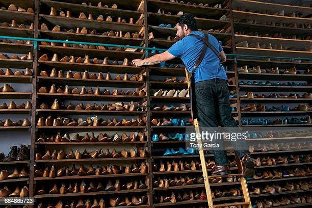male cobbler in traditional shoe shop on ladder selecting shoe last - shoemaker stock photos and pictures