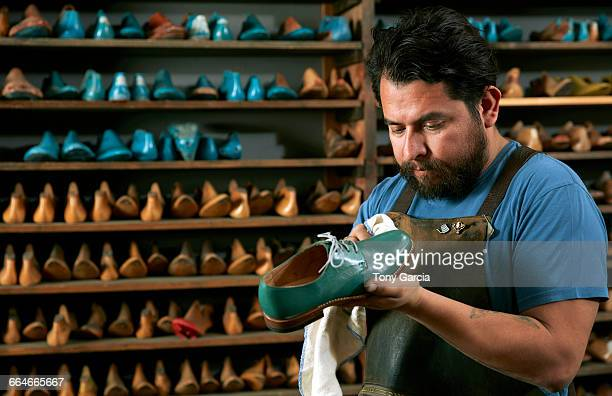 Male cobbler in traditional shoe shop polishing green brogue