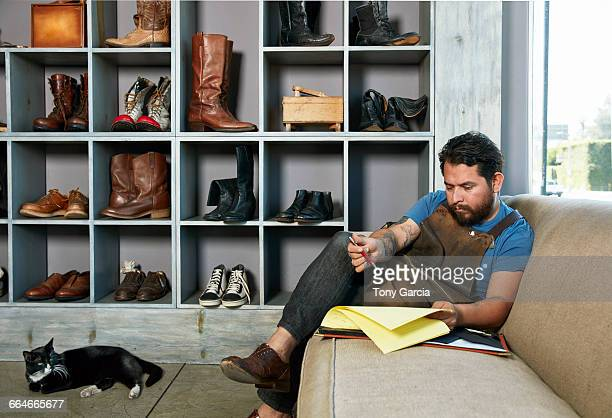 Male cobbler in traditional shoe shop sitting on sofa doing paperwork