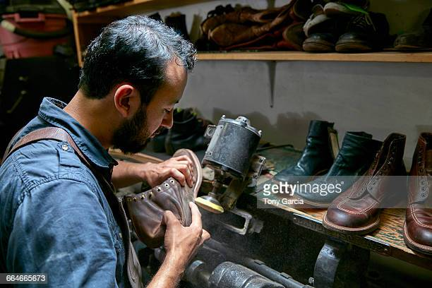 male cobbler in traditional shoe workshop inspecting boot - shoemaker stock photos and pictures