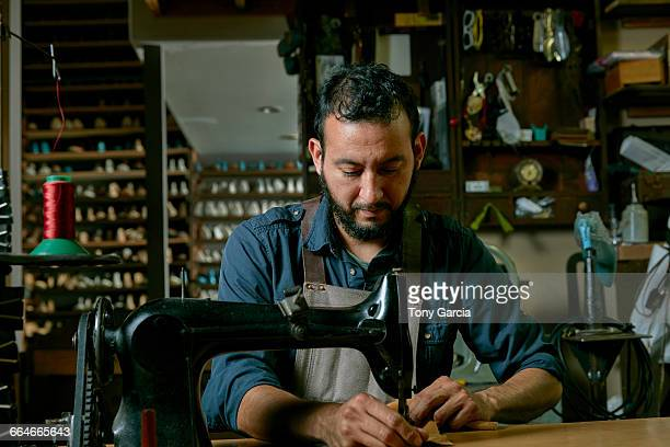 male cobbler working at sewing machine in traditional shoe workshop - shoemaker stock photos and pictures
