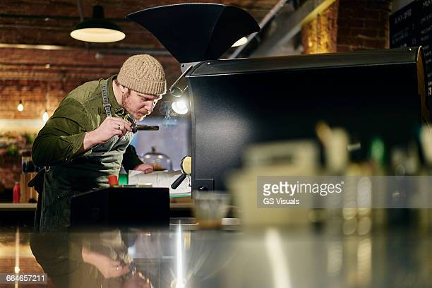 Male coffee shop owner smelling coffee from coffee roaster