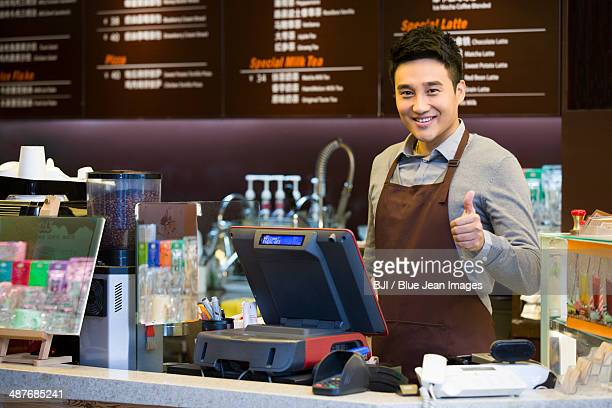 Male coffee store clerk doing thumbs up