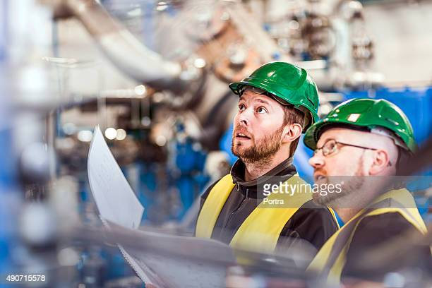 Male colleagues analysing machine in industry
