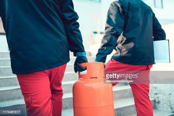 male colleagues checking broken gas cylinder - butane stock pictures, royalty-free photos & images