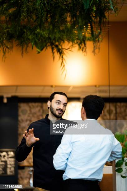 male colleagues discussing while standing at workplace - seulement des adultes photos et images de collection