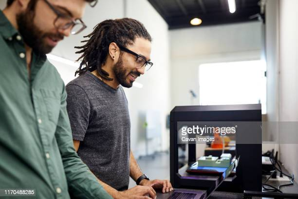 male colleagues discussing while standing in office - 3d printing stock pictures, royalty-free photos & images