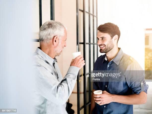 Männlichen Kollegen halten Einwegbecher im Büro