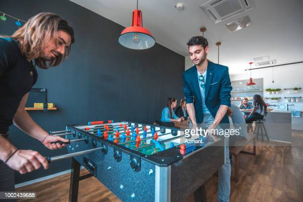 Male colleagues playing foosball in office