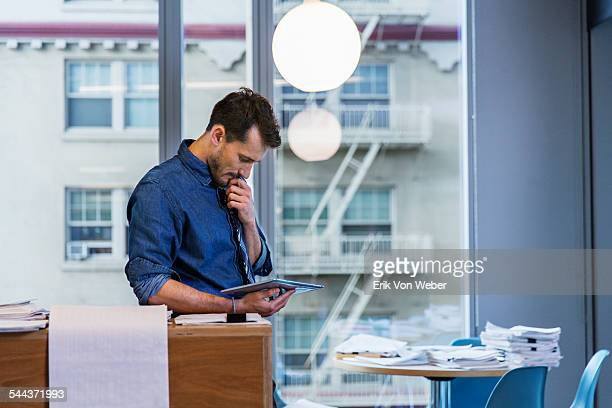 Male colleagues reading digital tablet