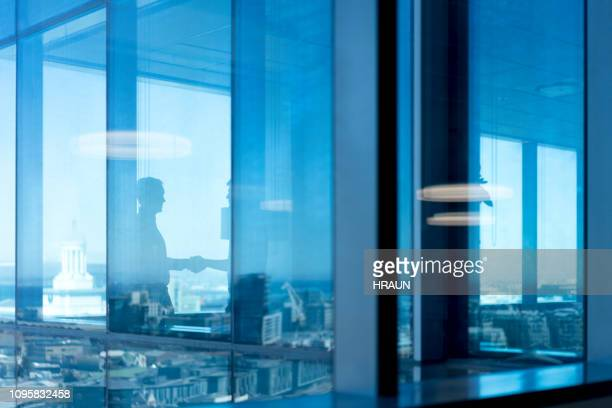 male colleagues shaking hands seen through glass - photographed through window stock pictures, royalty-free photos & images