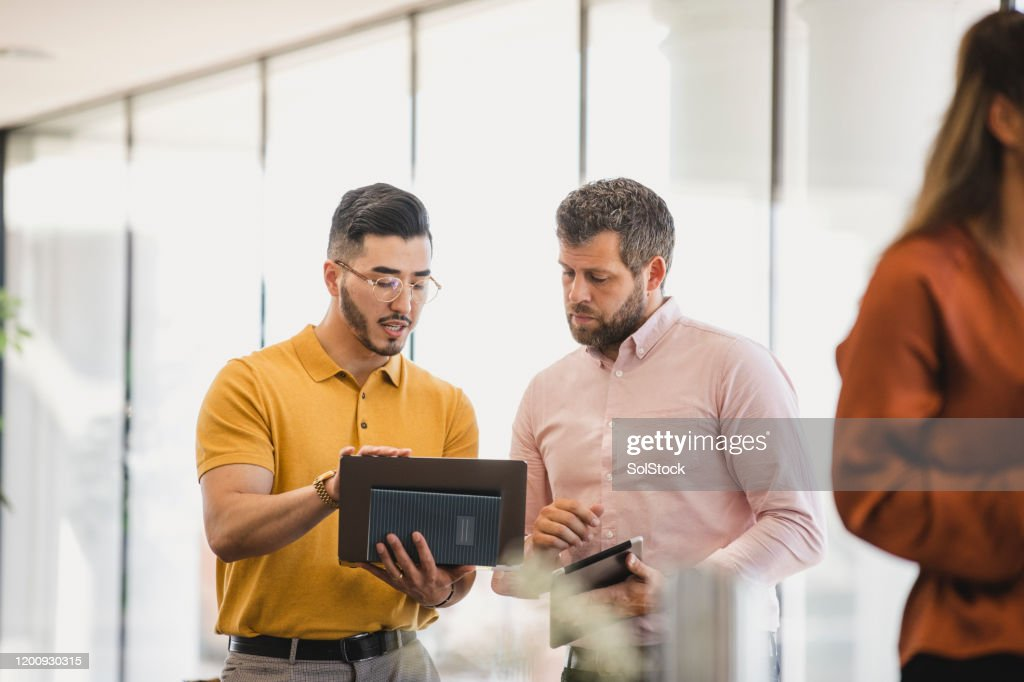 Male colleagues using laptop at business conference : Stock Photo