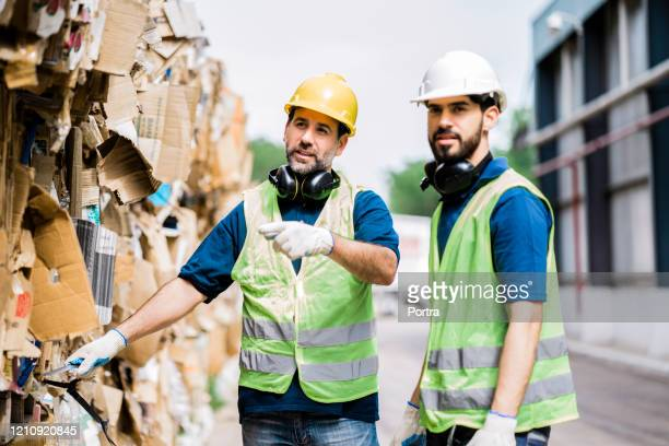 male colleagues working at recycling factory - waste management stock pictures, royalty-free photos & images