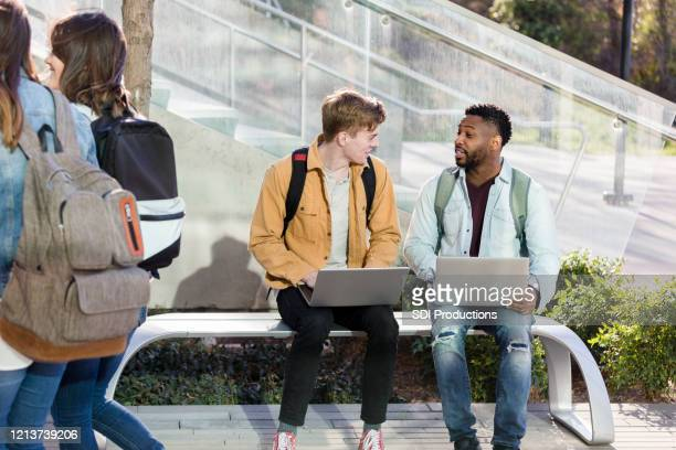 male college friends with laptops sit on bench outside - community college stock pictures, royalty-free photos & images
