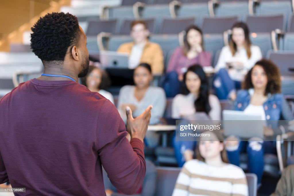 Male college professor gestures during lecture : Stock Photo