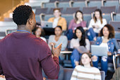 Male college professor gestures during lecture